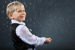 De glimlachende jongen bevindt zich in regen en vangt dalingen Stock Foto