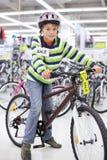 De glimlachende jongen in helm zit op fiets Royalty-vrije Stock Foto's