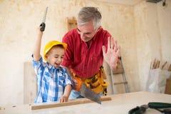 De glimlachende jongen helpt aan zijn granfather in workshop stock foto