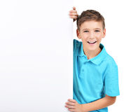 De glimlachende jongen kijkt uit van witte banner royalty-vrije stock foto