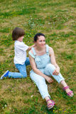 De glimlachende jongen verbetert moederkapsel in het park Royalty-vrije Stock Foto