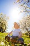 de glimlachende jongen zit op een gras onder zonstralen stock fotografie