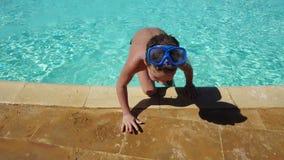De glimlachende jongen in zwemmend masker gaat van blauwe pool weg stock video