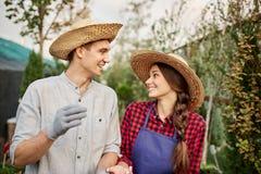 De glimlachende kerel en meisjestuinlieden in een strohoeden kijken aan elkaar in tuin op een zonnige dag royalty-vrije stock foto