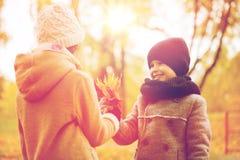 De glimlachende kinderen in de herfst parkeren Royalty-vrije Stock Foto's