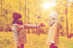 De glimlachende kinderen in de herfst parkeren Royalty-vrije Stock Afbeelding