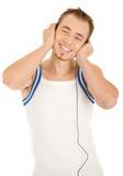 De glimlachende knappe mens is het luisteren muziek Stock Fotografie