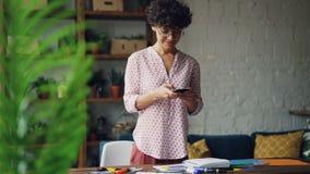 De glimlachende krullend-haired dame neemt beelden die van bureau tot vlakte leiden legt het gebruiken van smartphonecamera die z stock footage