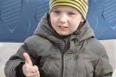 De glimlachende leuke Kaukasische babyjongen maakt omhoog zijn duimen Het dragen van toevallige, gele gestreepte hoed, kaki jasje royalty-vrije stock foto's