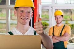 De glimlachende magazijnmeester die duimen tonen ondertekent omhoog stock afbeeldingen