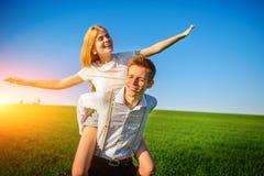 De glimlachende Man houdt op zijn achter gelukkige vrouw, die hij terugtrekt stock fotografie