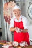 De glimlachende Mannelijke Slachterij van Slagersholding meat in stock afbeeldingen