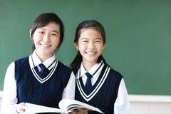 De glimlachende meisjes van de tienerstudent in klaslokaal royalty-vrije stock afbeeldingen