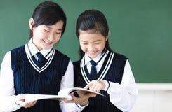 De glimlachende meisjes van de tienerstudent in klaslokaal royalty-vrije stock afbeelding