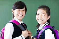 De glimlachende meisjes van de tienerstudent in klaslokaal stock foto