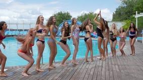 De glimlachende meisjes in zwempak hebben pret dichtbij poolside, menigte van vrouw bij de toevlucht, poolpartij, slanke meisjes  stock footage
