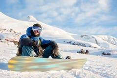 De glimlachende mens die snowboarder zit rusten Royalty-vrije Stock Fotografie