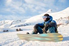 De glimlachende mens die snowboarder zit rusten Stock Afbeelding