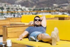De glimlachende mens die van de de zomervakantie genieten die op a leggen sunbed in een overzeese bar stock afbeelding