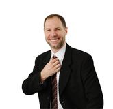 De glimlachende mens in een kostuum maakt zijn band recht Royalty-vrije Stock Afbeelding