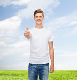 De glimlachende mens in het witte t-shirt tonen beduimelt omhoog Royalty-vrije Stock Foto