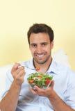 De glimlachende mens houdt van salade Stock Foto