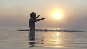 De glimlachende mens maakt golven in meerwateren in de zomer in slo-mo stock videobeelden