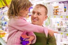 De glimlachende mens met meisje koopt yoghurt in supermarkt Stock Afbeeldingen