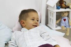 De glimlachende modieuze jongen ligt op het lichte bed stock foto's