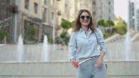 De glimlachende modieuze vrouw gaat vanaf het schot stock footage