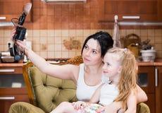 De glimlachende moeder en de dochter nemen een selfie stock afbeelding