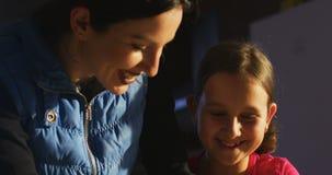 De glimlachende moeder en de dochter van het familie knedende deeg samen stock footage