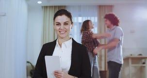 De glimlachende mooie vrouw die van het agentenhuis recht aan de camera kijken terwijl op achtergrond het paar gelukkig elk koest stock footage