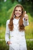 De glimlachende mooie vrouw heft duimen op naar omhoog, Stock Afbeeldingen