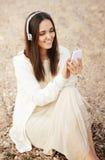 De glimlachende mooie vrouw ontspant het luisteren muziek met witte telefoon royalty-vrije stock fotografie