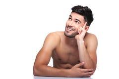 De glimlachende naakte schoonheidsmens kijkt omhoog aan zijn kant Stock Fotografie
