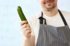 De glimlachende Organische Komkommer van Chef-kokholding raw green royalty-vrije stock foto