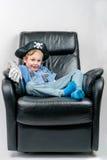 De glimlachende oude jongen van vijf jaar omhoog gekleed in een piraat en politiemankostuum zit en laze in een zwarte leerleunsto stock afbeelding