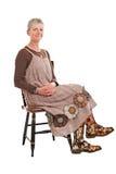 De glimlachende oudere vrouw zit in gebloeide laarzen Royalty-vrije Stock Afbeelding