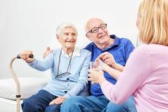 De glimlachende oudste neemt tablet met water stock foto's