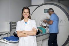 De glimlachende Patiënt van Artsenwith colleague preparing voor CT Aftasten stock afbeelding