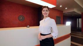 De glimlachende receptionnist bij het bureau van de hotelontvangst ontmoet gasten 4K stock videobeelden
