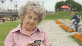 De glimlachende rijpe oude vrouw houdt een slimme telefoon stock video