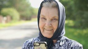 De glimlachende rijpe oude vrouw toont in openlucht smartphone stock video