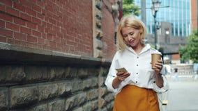 De glimlachende rijpe vrouw gebruikt smartphoneholding neemt koffie in openlucht lopend stock video