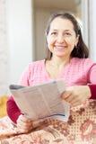 De glimlachende rijpe vrouw leest krant Stock Afbeeldingen