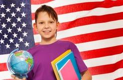 De glimlachende schooljongen leert aardrijkskunde met een bol Stock Afbeeldingen