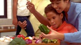 De glimlachende Spaanse familie kookt samen stock footage