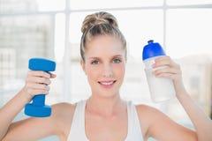De glimlachende sportieve fles en de domoor van de blondeholding Royalty-vrije Stock Foto's
