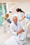 De glimlachende tandheelkundige toont model van tanden Stock Afbeeldingen